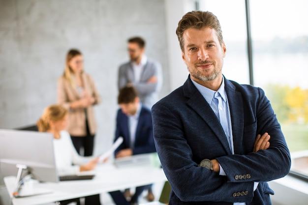 彼のチームの前のオフィスで自信を持って立っているハンサムな若いビジネスマン