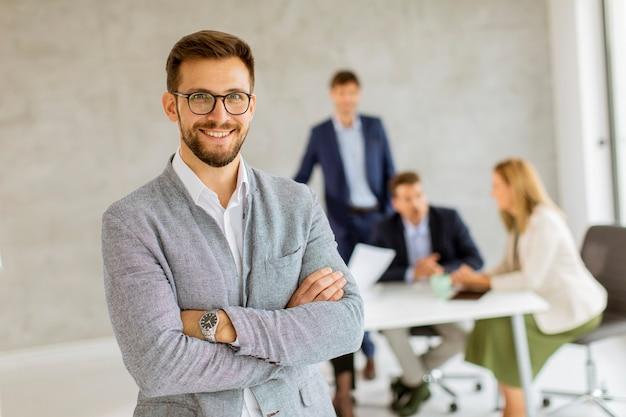 Красивый молодой деловой человек, уверенно стоящий в офисе перед своей командой
