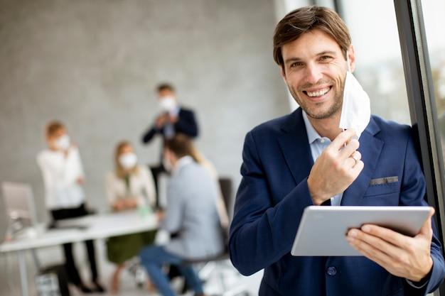 Красивый молодой деловой человек снимает защитную маску для лица, держа цифровой планшет в офисном помещении