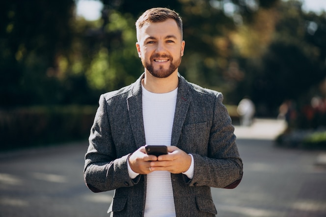 Handsome young business man using phone outside the street