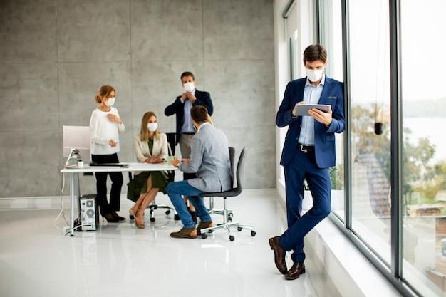 Красивый молодой деловой человек в защитной маске для лица, держа цифровой планшет в офисном помещении