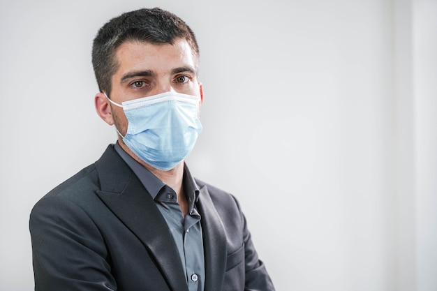 흰색 바탕에 보호 마스크를 쓴 잘생긴 젊은 사업가