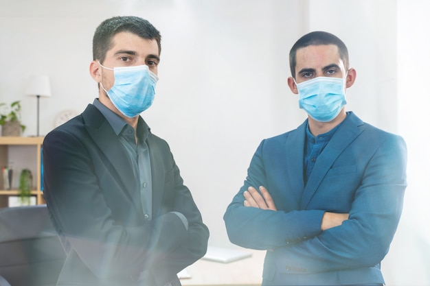 Handsome young business man wearing protective mask in a white background