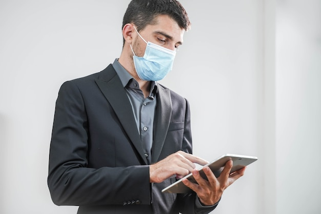 흰색 배경에서 태블릿으로 작업하는 보호 마스크를 쓴 잘생긴 젊은 사업가