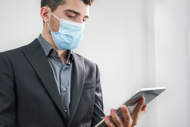 Handsome young business man wearing protective mask working with tablet in a white background