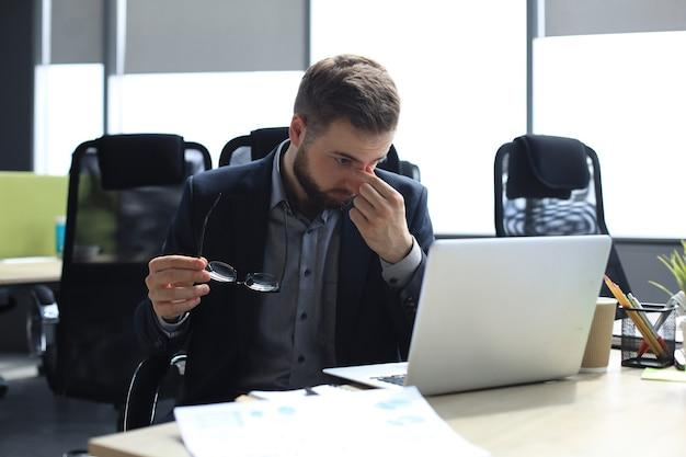 Красивый молодой деловой человек с закрытыми глазами, касаясь лица руками, сидя на рабочем месте в офисе.