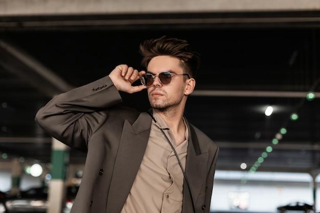 ファッショナブルな服を着た髪型のハンサムな若いビジネスマンは、サングラスをまっすぐにし、通りを歩きます。男性のカジュアルなスタイルとファッション