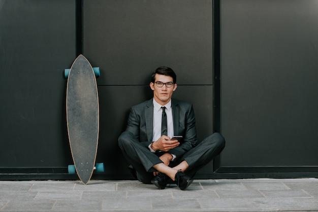 Красивый молодой деловой человек с его современным longboard