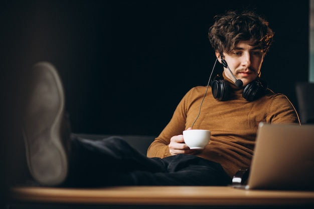 Handsome young business man working on computer and drinking coffee
