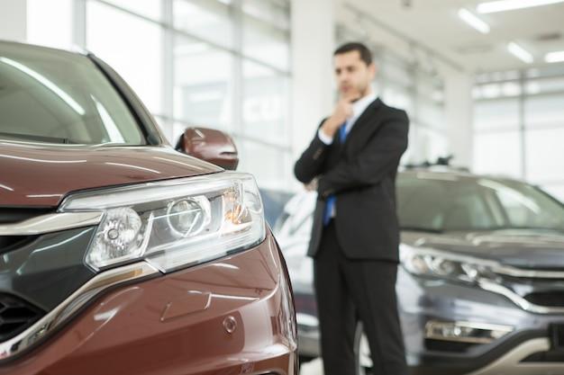 Красивый молодой бизнесмен, выбирая новый автомобиль в автосалоне