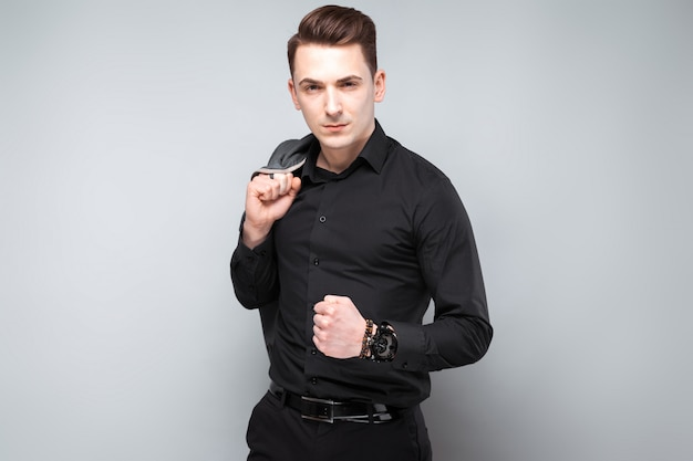 Handsome young businessman in costly watch and black shirt hold grey jacket