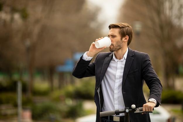 Красивый молодой бизнесмен, пьющий кофе на вынос на электросамокате