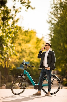 Handsome young businessman on the ebike using mobile phone