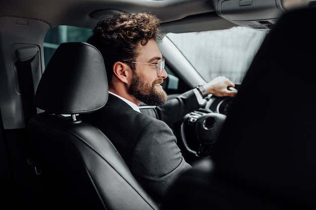 Handsome young businessman in full suit smiling while driving a new car