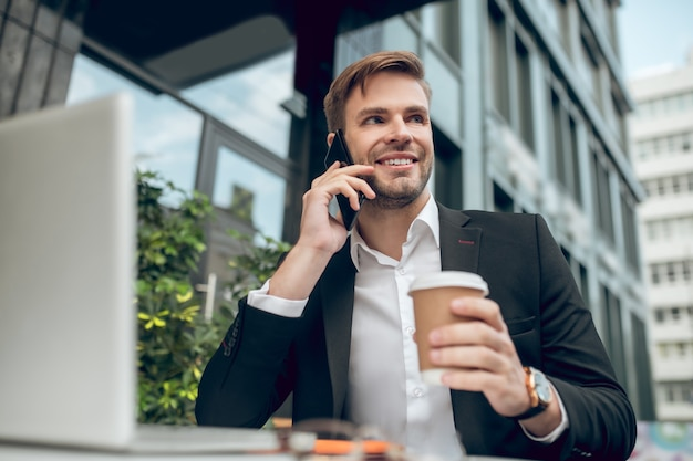Handsome young businessman having coffee and talking on the phone