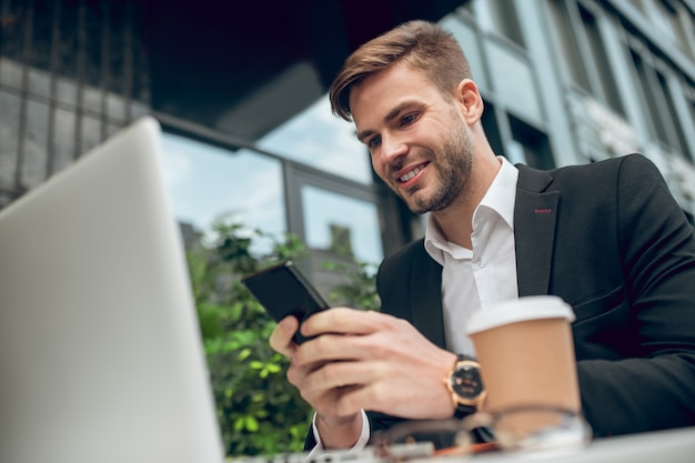 Handsome young businessman having coffee and texting
