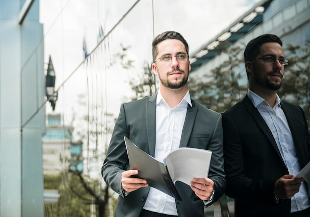 Handsome young businessman holding folder in hand looking away