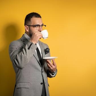 Красивый молодой бизнесмен в очках в формальной одежде, держа чашку кофе