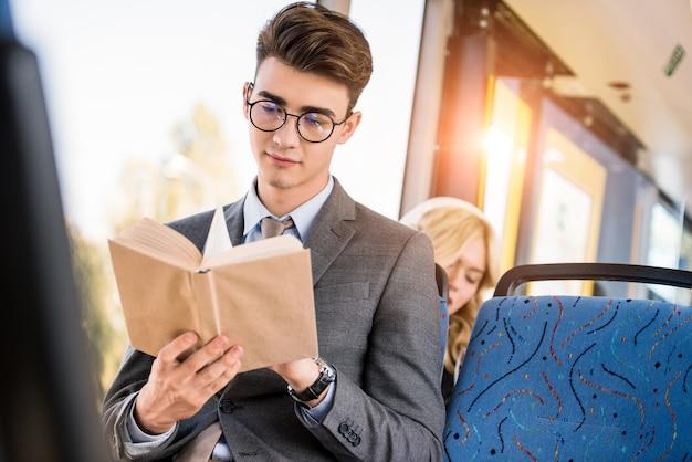市バスで本を読んで眼鏡のハンサムな青年実業家