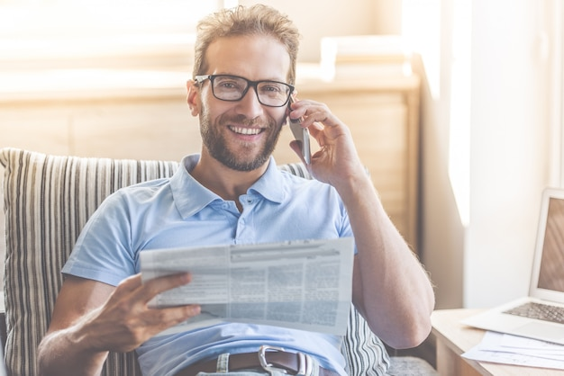 Handsome young businessman is reading newspaper