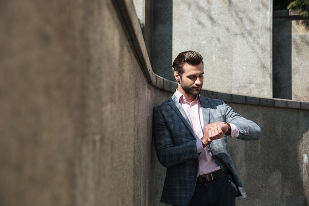 Bel giovane imprenditore guardando orologio.
