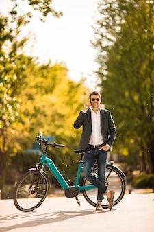 携帯電話を使用して電動自転車でハンサムな青年実業家
