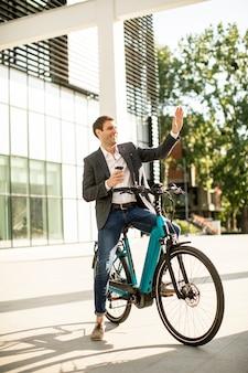 持ち帰り用コーヒーカップと電動自転車でハンサムな青年実業家