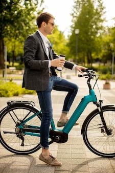 持ち帰り用のコーヒーカップと電動自転車でハンサムな青年実業家