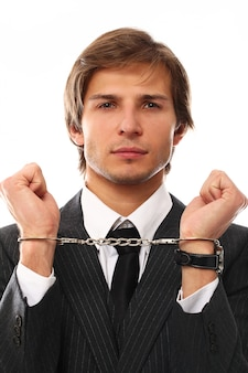 Handsome young businessman portrait with handcuffs