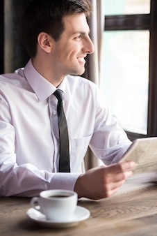 Handsome young businessman reading newspaper.