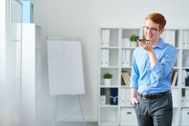 ハンサムな青年実業家の休憩時間に口でスマートフォンを押しながら彼の声を記録