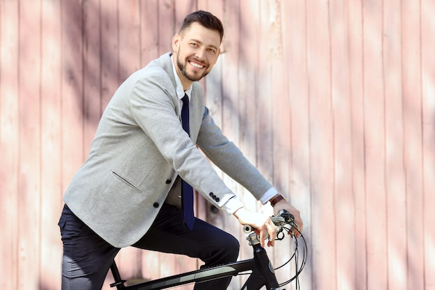 화창한 날 야외에서 자전거를 타고 잘 생긴 젊은 사업가