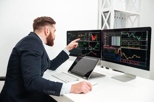 사무실에 앉아서 컴퓨터 작업을 하는 잘생긴 젊은 사업가