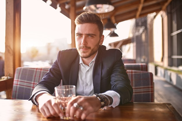 Handsome young businessman sitting in a summer outdoor cafe