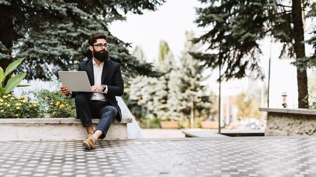 Handsome young businessman sitting with laptop in the park looking away