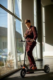Красивый молодой бизнесмен, стоя у окна офиса с электросамокатом