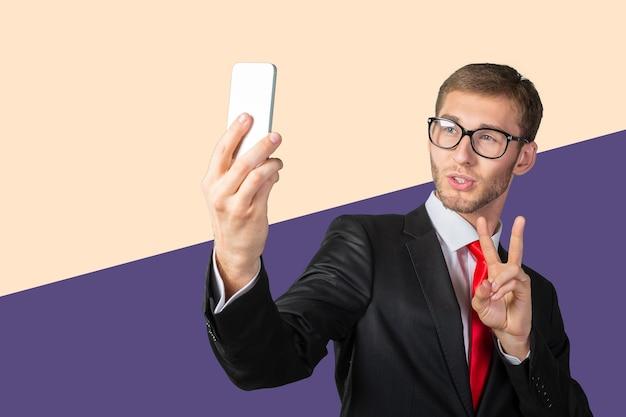 携帯電話で自分撮りをしているハンサムな青年実業家