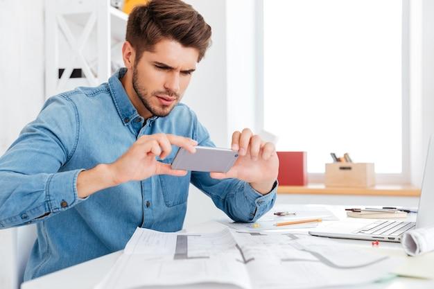 Красивый молодой бизнесмен фотографирует документы со смартфоном, сидя за офисным столом