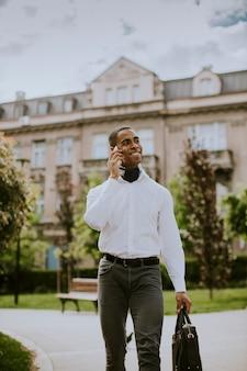 Красивый молодой бизнесмен с помощью мобильного телефона во время ожидания такси на улице