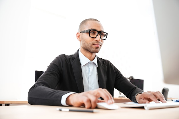 Handsome young businessman using computer for work at the office
