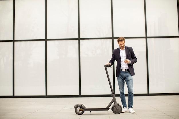 Красивый молодой бизнесмен с помощью мобильного телефона на электросамокате Premium Фотографии