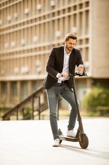 電動スクーターで携帯電話を使用してハンサムな青年実業家