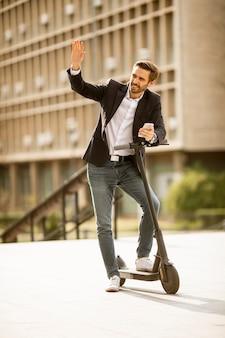 Красивый молодой бизнесмен с помощью мобильного телефона на электросамокате