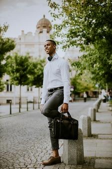 Красивый молодой бизнесмен waitng такси на улице