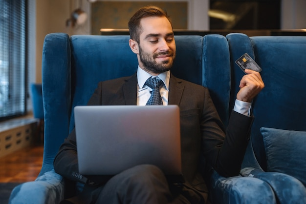 Handsome young businessman wearing suit sitting at the hotel lobby, using laptop computer, showing plastic credit card