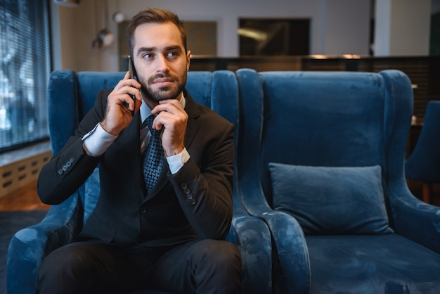 Handsome young businessman wearing suit sitting at the hotel lobby, using mobile phone, celebrating success