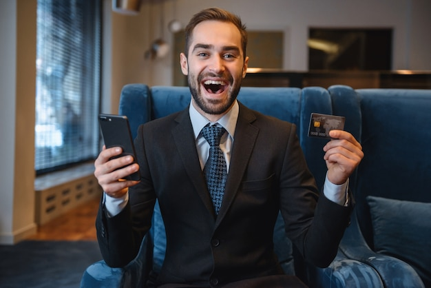 Handsome young businessman wearing suit sitting at the hotel lobby, using mobile phone, showing plastic credit card