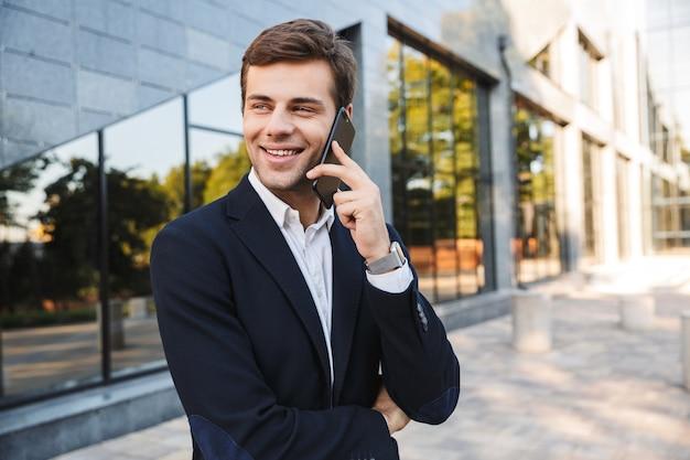 야외에서 걷고, 휴대 전화를 사용하여, 가방을 들고 양복을 입고 잘 생긴 젊은 사업가