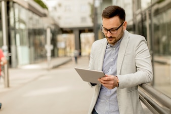 Handsome young businessman with digital tablet by the office building