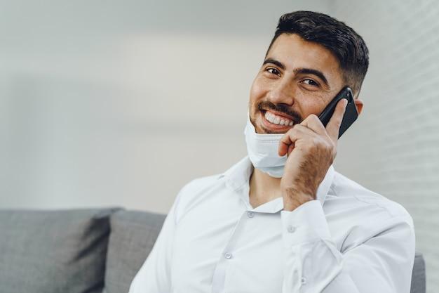 Красивый молодой бизнесмен с маской, разговаривает по телефону, портрет